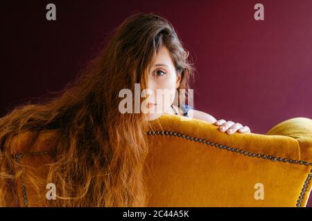 Portrait rapproché de la jeune femme avec de longs cheveux bruns, adochée sur une chaise dorée sur un fond coloré