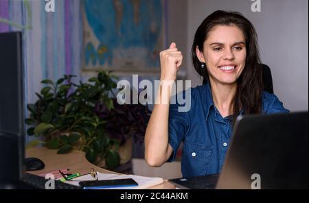 Une jeune femme surjoyeuse en denim travaillant à la maison avec un ordinateur portable et en étirant les bras pour obtenir de bonnes nouvelles ou gagner du succès. Carte du monde dans