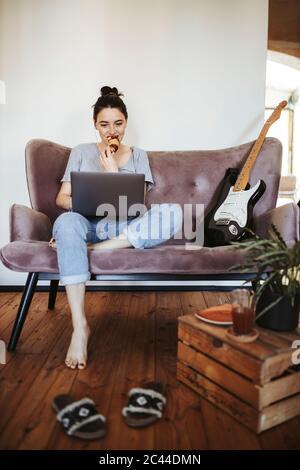 Une jeune femme assise sur un canapé à la maison mangeant un croissant tout en regardant un ordinateur portable Banque D'Images