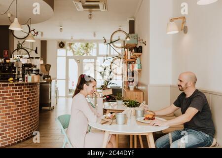 Homme et femme souriants assis à une table dans un café