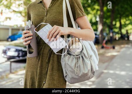 Gros plan d'une femme tenant un masque facial et une bouteille de boisson dans sa main tout en marchant vers son club de santé Banque D'Images