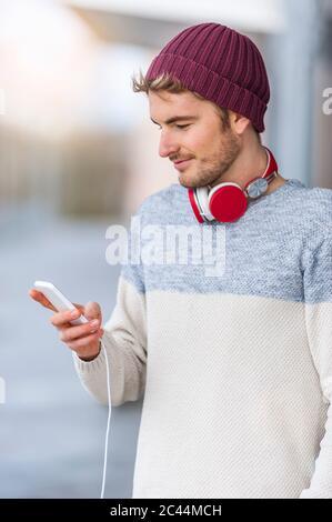 Jeune homme élégant utilisant un smartphone en extérieur Banque D'Images