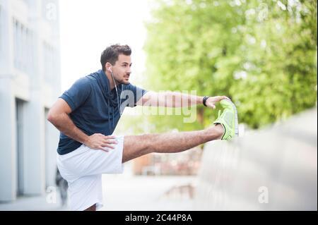 Jeune homme qui s'étire la jambe sur le mur dans la ville