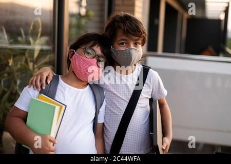 Frères et sœurs avec des livres portant des masques à l'extérieur