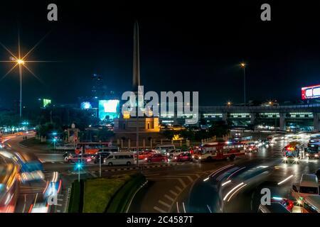 Vue nocturne du monument de la victoire dans le quartier Ratchathewi de Bangkok, en Thaïlande, avec beaucoup de circulation au rond-point Banque D'Images