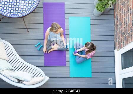 Vue de la tête de la mère et de la fille se reposant et bavardant après avoir fait de l'exercice ensemble à la maison sur le pont Banque D'Images