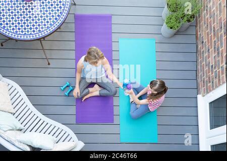 Vue en hauteur de la mère et de la fille donnant entre eux des cheers avec bouteille d'eau après avoir fait de l'exercice ensemble à la maison sur le pont Banque D'Images