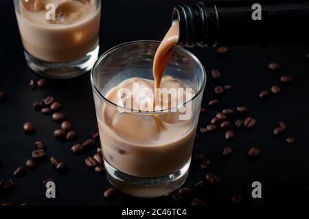 Verser de la crème irlandaise dans un verre de glace, entouré de grains de café sur un fond noir foncé