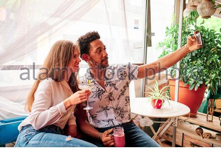 jeune couple interracial amoureux de prendre le selfie au bar Banque D'Images
