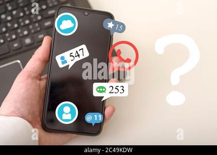 La main utilise un smartphone et un hologramme de diverses icônes, dont un point d'interrogation. Concepts de réseaux sociaux.