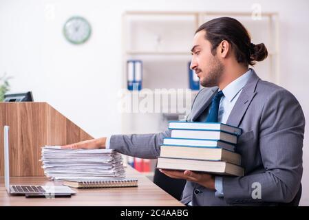 Un jeune homme d'affaires lit des livres sur son lieu de travail Banque D'Images
