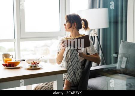 Photo de jeune femme concentrée lisant le livre tout en prenant le petit déjeuner dans une chambre confortable à la maison Banque D'Images