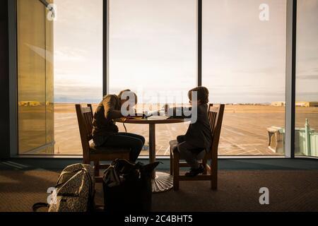 Un garçon et sa sœur aînée s'asseoir à une table dans un salon de l'aéroport, écrire et dessiner.