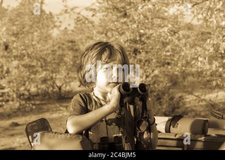 Un garçon de cinq ans tenant des jumelles debout dans une jeep à toit ouvert dans un bois. Banque D'Images