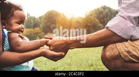 Bonne famille africaine s'amuser ensemble dans le parc public - le père noir et la mère tenant la main avec leur fille Banque D'Images