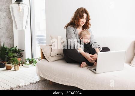 Jeune femme magnifique assise sur un canapé avec son petit fils charmant utilisant un ordinateur portable ensemble. Maman avec bébé garçon heureux de passer du temps dans la vie