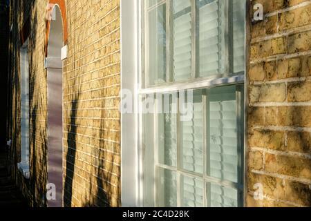 Soleil du soir extérieur d'une grande maison en brique construite en terrasse vu dans le soleil chaud d'hiver. Des flocons de neige peuvent être vus attachés à la fenêtre. Banque D'Images