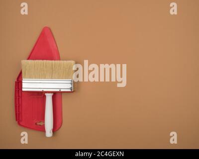 Spatule pour lisser le papier peint et un grand pinceau. Arrière-plan beige.
