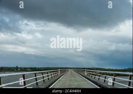 Pont routier à voie unique au-dessus de la rivière Haast, parc national de Westland, Nouvelle-Zélande. Route vide s'étendant jusqu'au point de fuite avec ciel de nuages moody