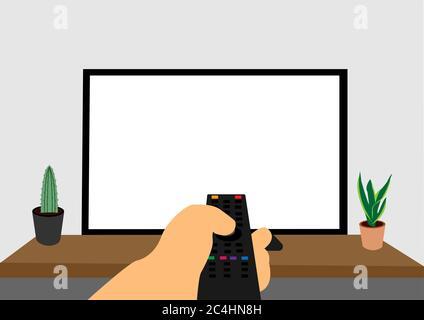Téléviseur grand écran sur un bureau et un homme l'utilisant avec la télécommande. Banque D'Images