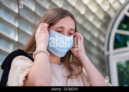 fille mettant sur le masque pour éviter le virus