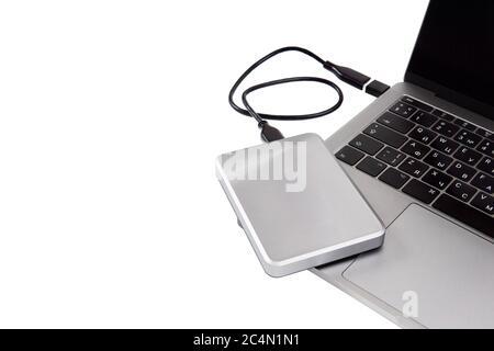 disque dur portable couleur argent connecté à un ordinateur portable via un câble usb. Isolé sur blanc, espace de copie. Concept de stockage de données ou de sauvegarde système. Banque D'Images