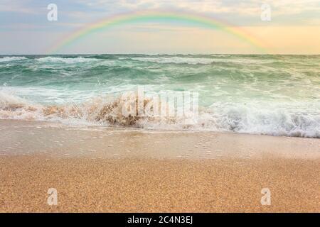 tempête sur la plage de sable au coucher du soleil. paysage océanique spectaculaire avec ciel nuageux. arc-en-ciel au-dessus de l'eau brute et vagues écrasant dans la lumière du soir