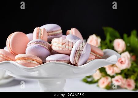 macarons sur un plateau blanc avec beau bouquet de roses sur fond noir, vue horizontale, gros plan, espace libre Banque D'Images