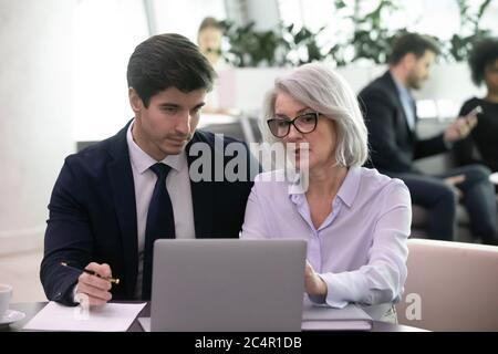 Une femme d'affaires mature utilise un ordinateur portable pour discuter de son plan d'affaires avec un collègue plus jeune Banque D'Images