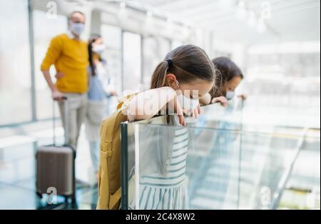 Famille avec deux enfants en vacances, portant un masque facial à l'aéroport.
