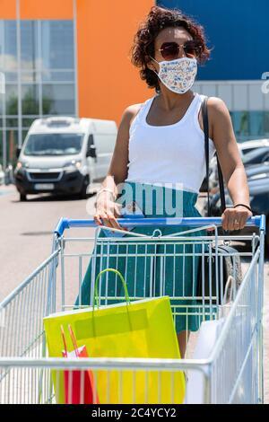 Femme portant un masque de protection poussant le chariot dans le stationnement du centre commercial. Concept de shopping dans la nouvelle norme.