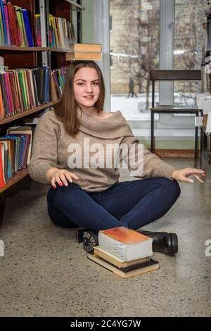 Petite fille brunette assise sur le sol et de l'équilibre de la pile de livres sur sa tête près de la bibliothèque Banque D'Images