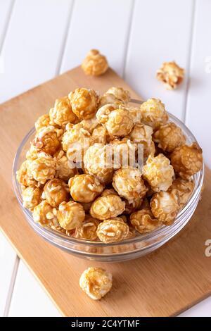 Pop-corn au caramel sucré dans un bol en verre. Gros plan. Arrière-plan en bois clair. Banque D'Images