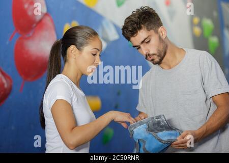 femme et homme grimpeur qui enduction les mains de craie en poudre Banque D'Images