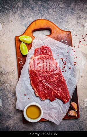 Viande de bœuf crue aux épices sur bois, fond sombre, espace de copie.