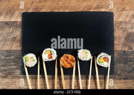 Ensemble de rouleaux à sushis avec baguettes. Place pour votre texte ou logo.
