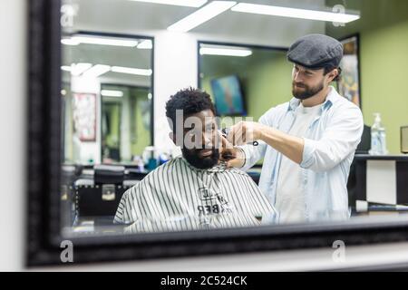 Jeune homme noir heureux en train d'être tondu avec une tondeuse électrique dans un salon de coiffure. Concept de soins de beauté pour hommes. Jeune homme africain souriant, qui devient nouveau