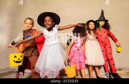 Fille avec seau de bonbons sur le groupe d'enfants dans les costumes d'Halloween Hug debout ensemble et souriant regardant l'appareil photo Banque D'Images