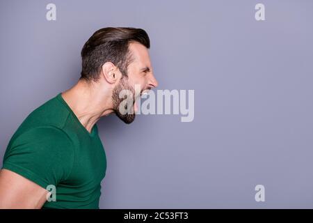 Profil photo de attrayant fou gars soigneux cheveux soil yelling furious côté vide espace combat avec petite amie nerveux mauvaise humeur porter décontracté vert