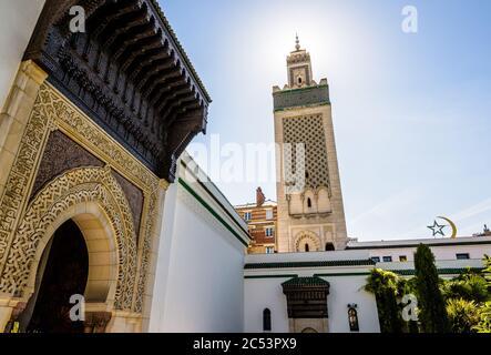 Vue à angle bas du minaret de la Grande Mosquée de Paris, vue en contre-jour depuis le jardin avec une porte et l'étoile et le croissant. Banque D'Images