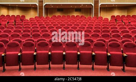 Vue panoramique sur une salle de cinéma vide. Rangées de sièges de théâtre rouges. Panorama de l'intérieur moderne du cinéma. Chaises confortables dans la salle de conférence