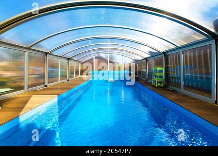 Piscine avec eau bleue et tente en plastique transparent. Style moderne de la piscine avec mur et toit pliants. Belle piscine contemporaine dans la cour de la maison Banque D'Images