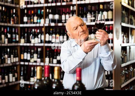 Portrait d'un homme expérimenté qui goûtant du vin rouge à la boutique de vins Banque D'Images