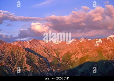 Vallée de montagne grandiose avec crêtes de sommets enneigés au coucher du soleil Banque D'Images