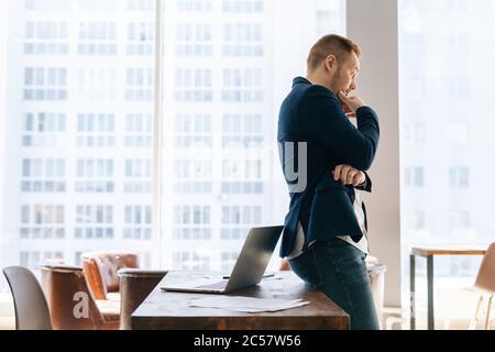 Vue latérale d'un jeune homme d'affaires attentionné portant des vêtements de costume dans une salle de bureau moderne