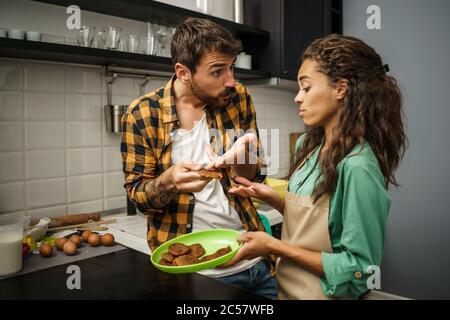 Le couple multiethnique est malheureux parce que les cookies qu'ils ont faits sont brûlés.