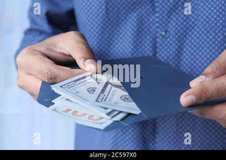 personne mettant de l'argent dans une enveloppe. Banque D'Images