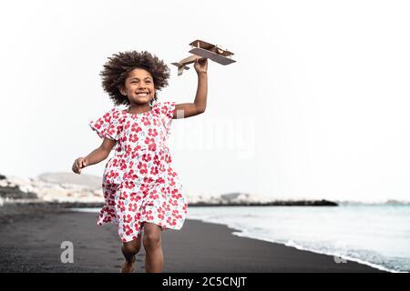 Enfant afro jouant avec un avion en bois sur la plage - petit enfant s'amusant pendant les vacances d'été - concept de vacances d'enfance et de voyage