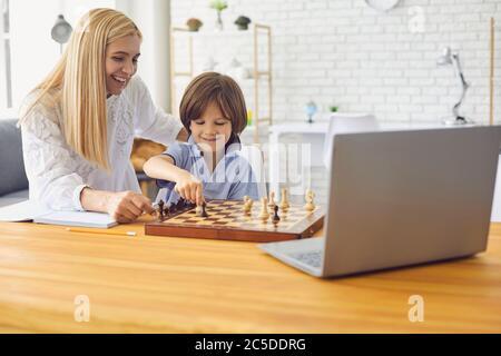 Mère enseignant son pour jouer aux échecs après la leçon en ligne sur ordinateur portable à la maison. Jeu de société pour parents et enfants Banque D'Images