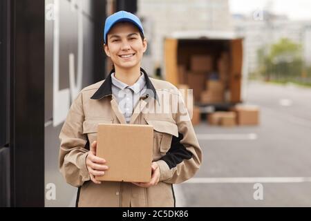 Portrait de la jeune femme en uniforme tenant le colis et souriant à la caméra tout en se tenant près de l'entrepôt